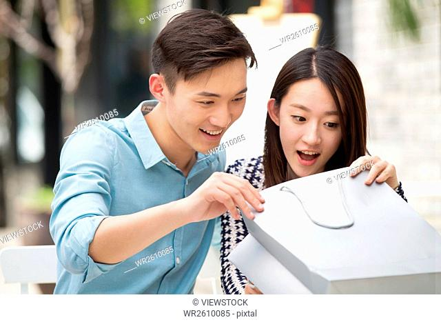 Young couple sitting in a cafe watching a gift