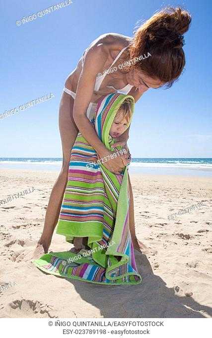 summer family scene of two woman mother hands wrapping and drying a two years blonde baby in colorful towel at beach sand