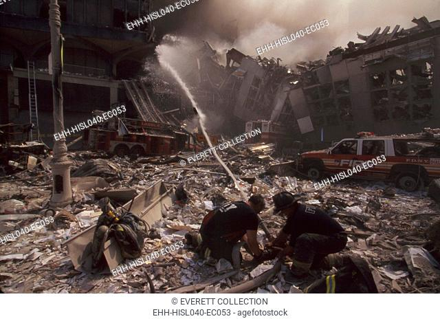 Fire fighters set up a hose amid smoking rubble following September 11th terrorist attack on World Trade Center. At left is still standing WTC 6