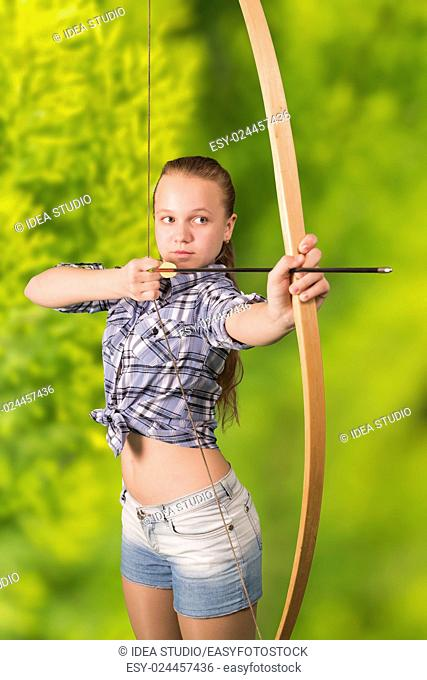 Teen girl practicing archery on green natural background
