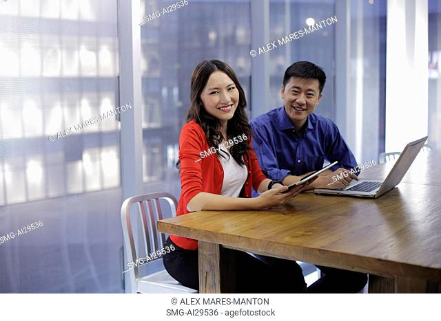 Young man and woman working on tablet and laptop