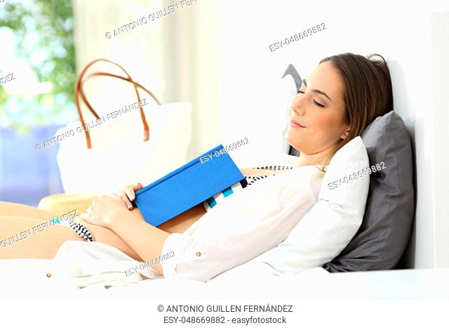 Relaxed woman sleeping with a book on chest in an hotel room on summer vacations