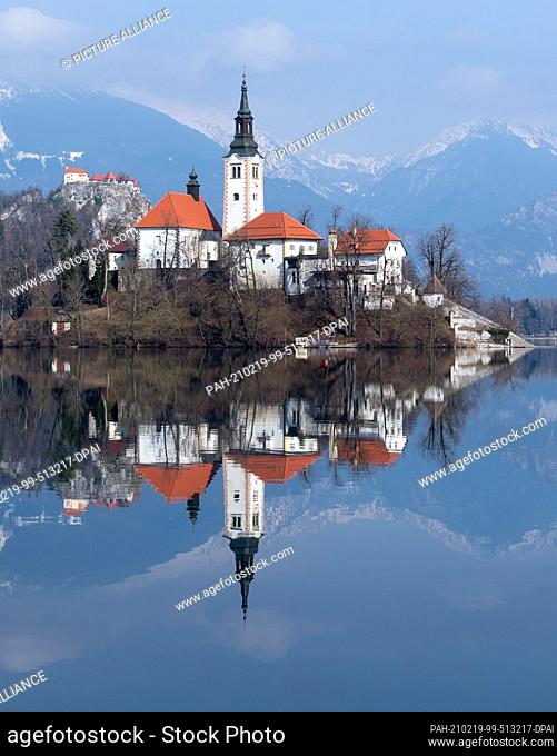 19 February 2021, Slovenia, Bled: The Church of the Assumption of the Virgin Mary on the island of Blejski Otok in Lake Bled at the foot of the Pokljuka plateau