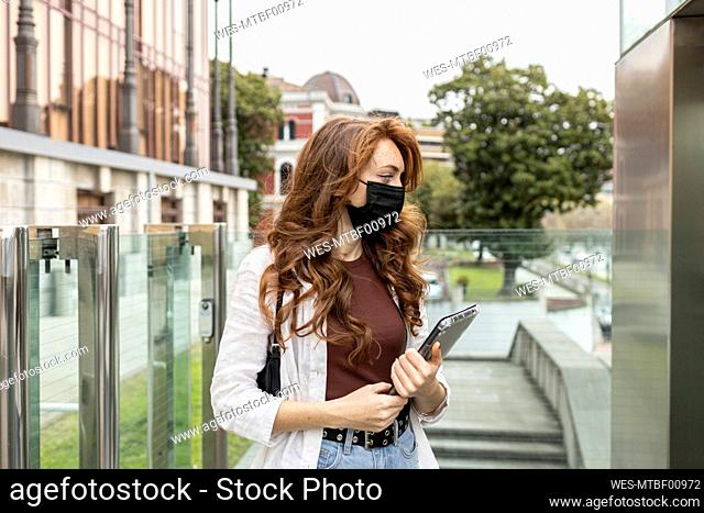 Young woman wearing protective face mask standing with digital tablet