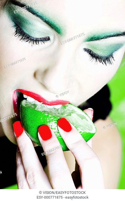 beautiful woman portrait with colorful make-up and background biting citrus fruit