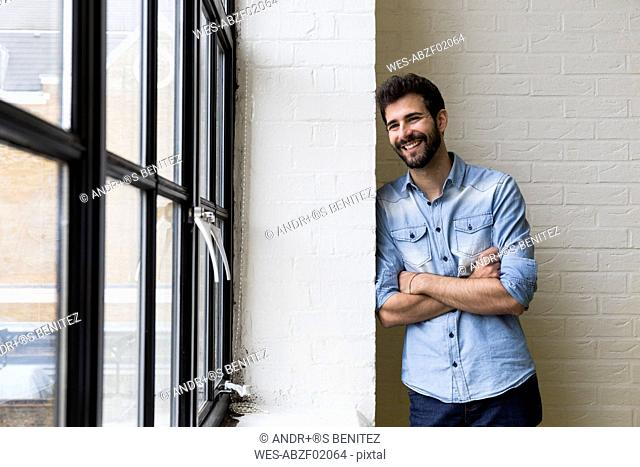 Smiling man leaning against a wall in his loft looking through window