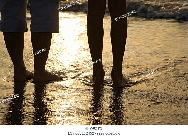 Caucasian women standing barefoot on beach in water