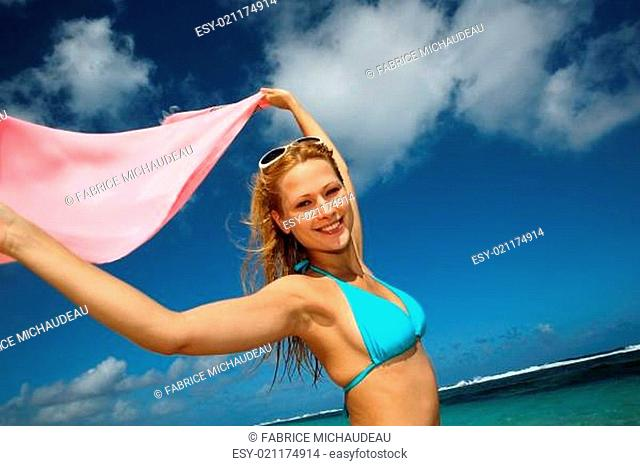 Attractive girl at the beach with pareo in the wind