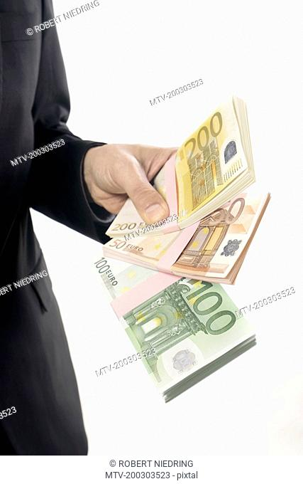 Businessman holding Euro banknotes, Bavaria, Germany