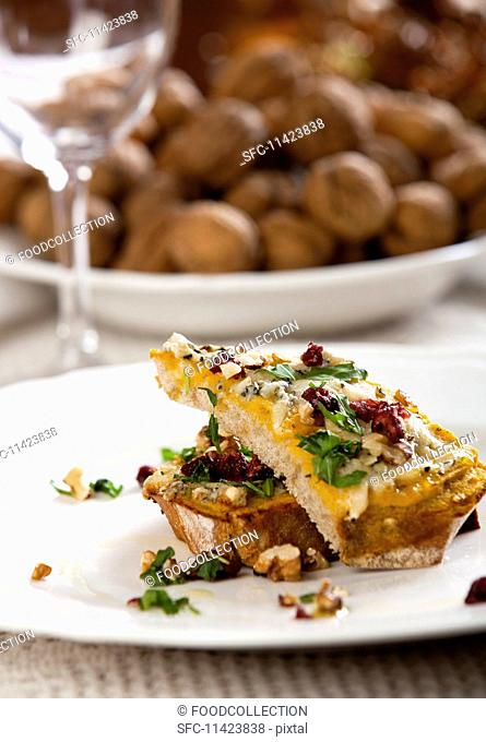 Slices of bread topped with mushrooms, nuts and cheese