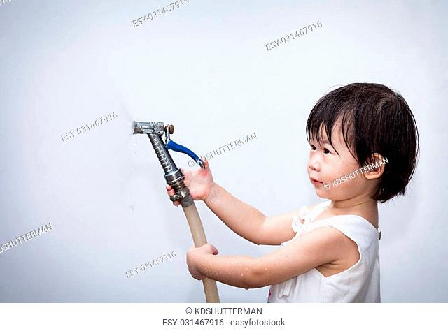 Adorable little asian (thai) girl play with water hose on wall white background