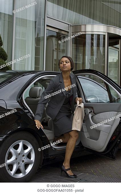 Businesswoman emerging from backseat of expensive car