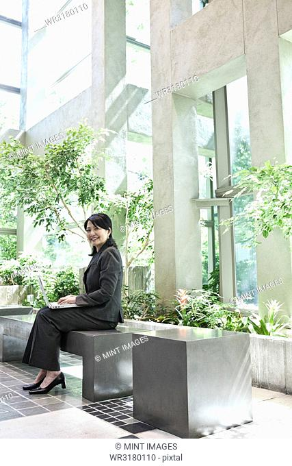 Asian businesswoman working in a large open lobby area