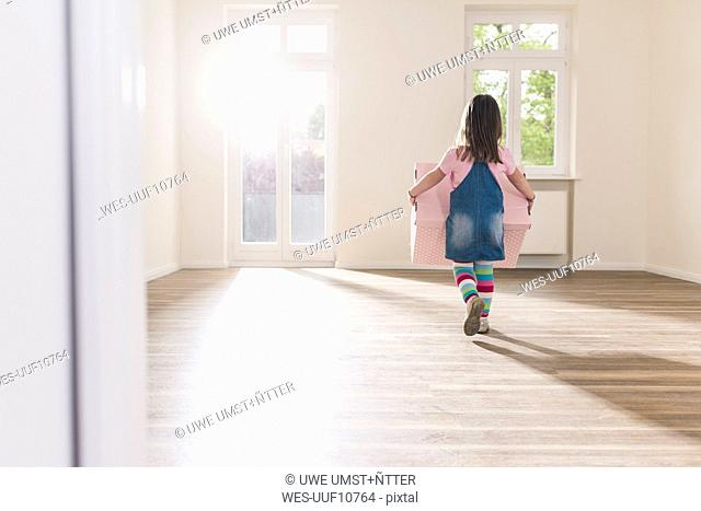 Girl carrying cardboard box in empty apartment