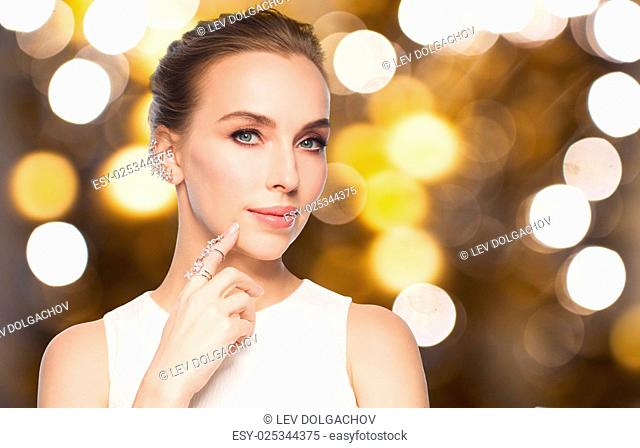 jewelry, luxury, wedding, holidays and people concept - beautiful woman in white dress with diamond ring and earring over lights background