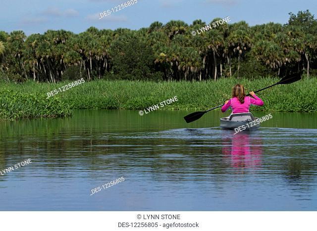 Woman kayaking in Upper Myakka River Lake, Myakka River State Park; Sarasota, Florida, United States of America