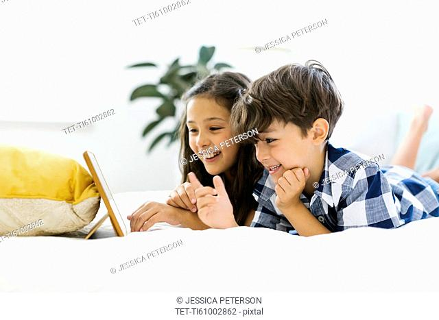 Siblings (10-11, 6-7) lying in bed and using tablet