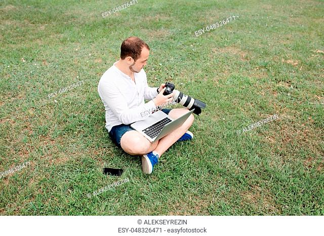 Young man photographer using laptop and camera in the park on a summers day