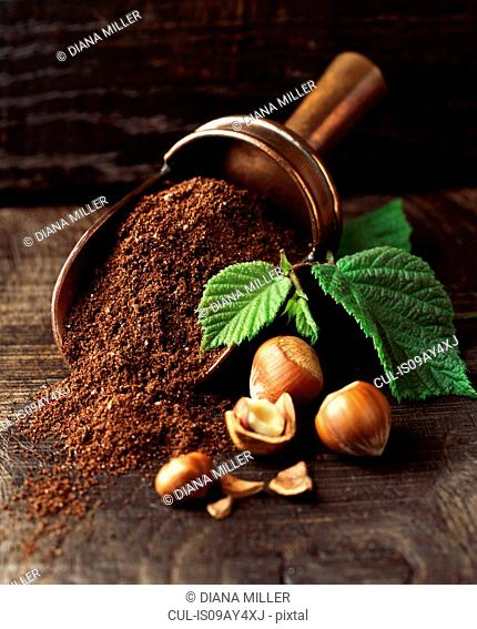 Hazelnuts and ground coffee in metal scoop