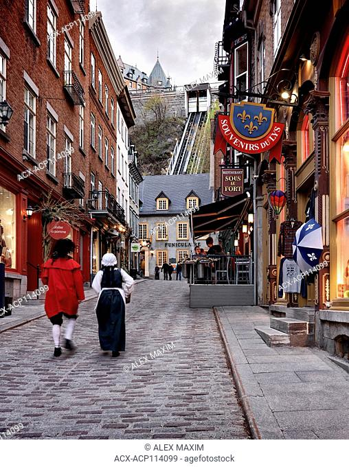 Two people in medieval costumes walking up the Rue Sous Le Fort street in old Quebec City with funicular in the background
