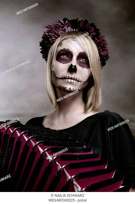Portrait of woman with sugar skull makeup and accordion
