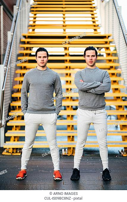 Young adult male twins training together, stairway portrait