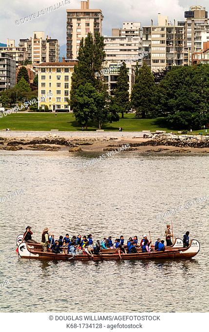 children paddle two large canoes toward False Creek, Vancouver, BC, Canada
