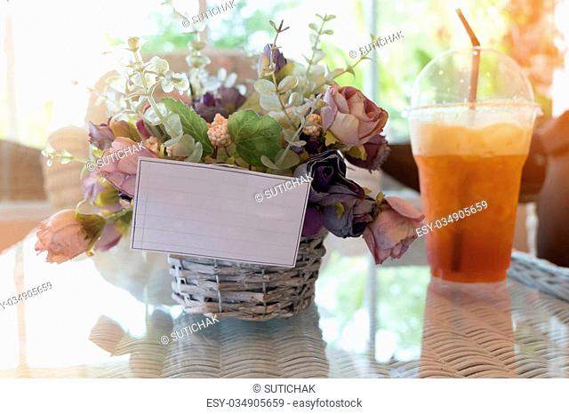 white paper blank on flowers vase decorated in cafe