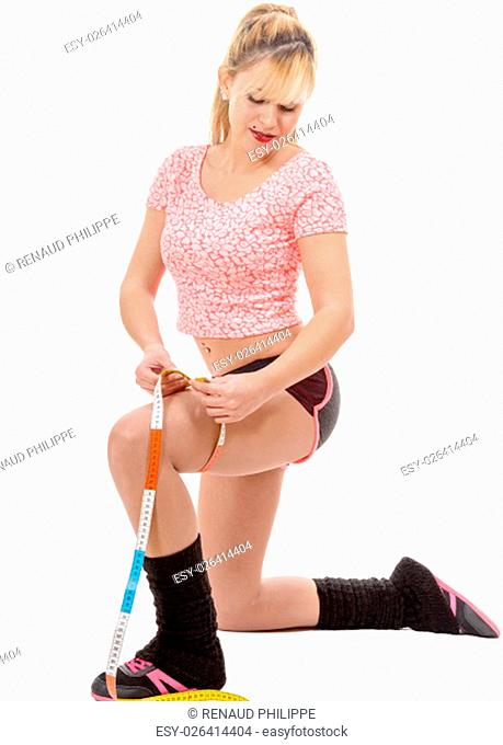 a fitness sporty woman measuring her thigh with a measuring tape