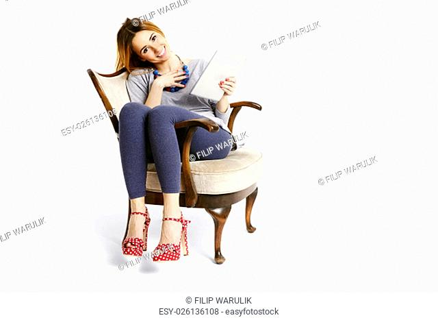 Young woman sitting on an a retro chair with tablet reading, smilling and feeling peaceful