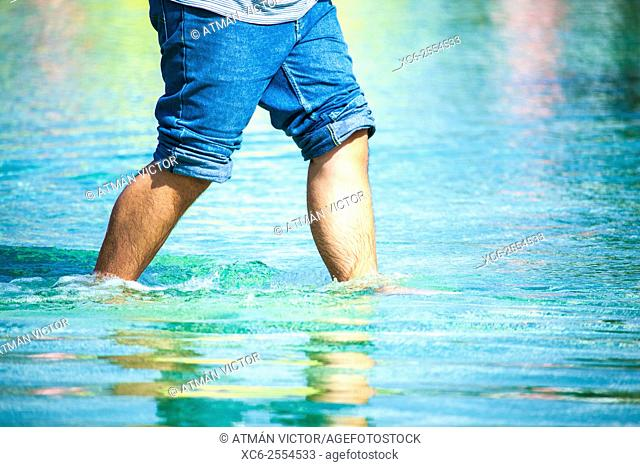 young man walking in a water pond with rolled up jeans