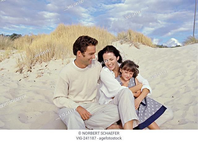portrait, brunette family wearing bright colours with their 5 years old daughter is sitting in tied embracement at the beach  - GERMANY, 27/01/2004