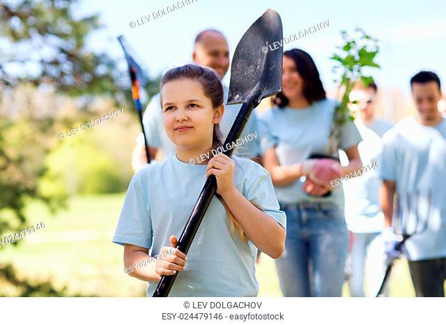 volunteering, charity, people and ecology concept - group of happy volunteers with tree seedlings and rake walking in park