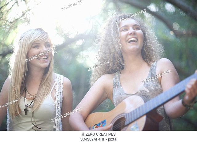 Two teenage girls playing guitar in woodland
