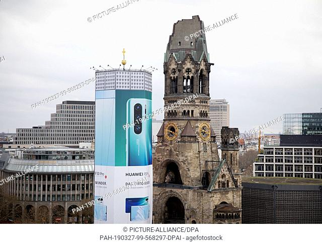 27 March 2019, Berlin: A huge advertising banner hangs on the bell tower of the Berlin Gedächtniskirche. For six months, the tower will be covered by...