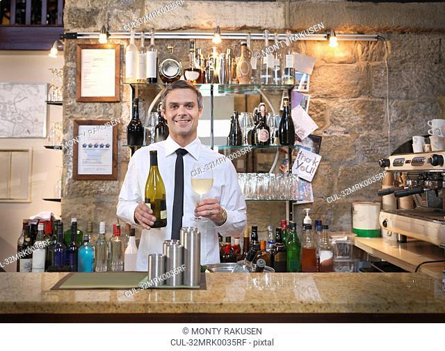 Host offering wine in restaurant