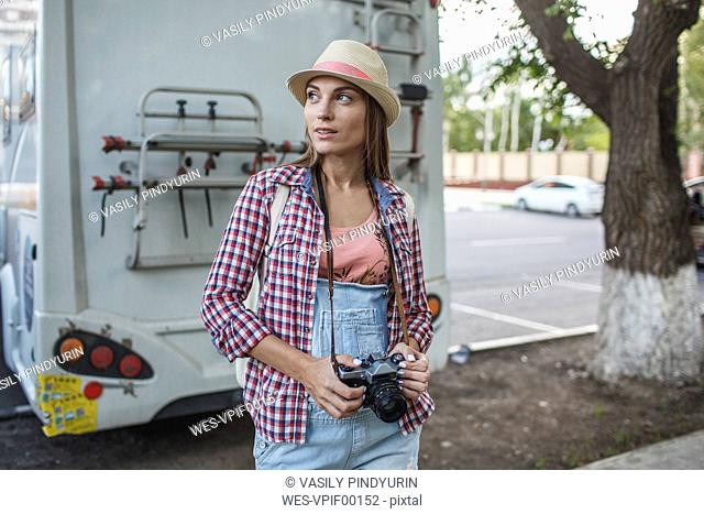 Young woman with a camera on car park looking around