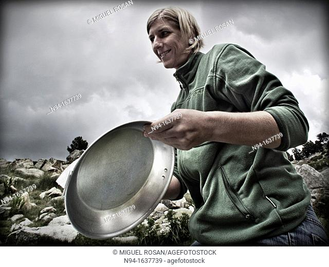 Young blonde woman preparing aluminum plates on the mountain