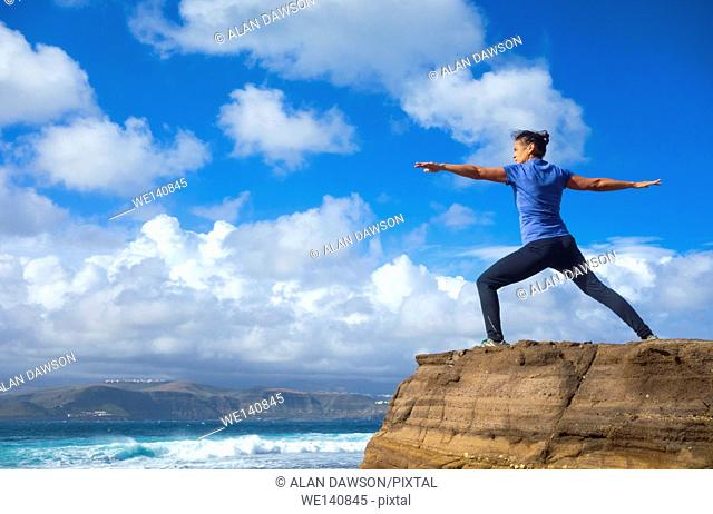 Mature female jogger warming up with Yoga stretching exercises at El Confital beach, Las Palmas, Gran Canaria, Canary Islands, Spain