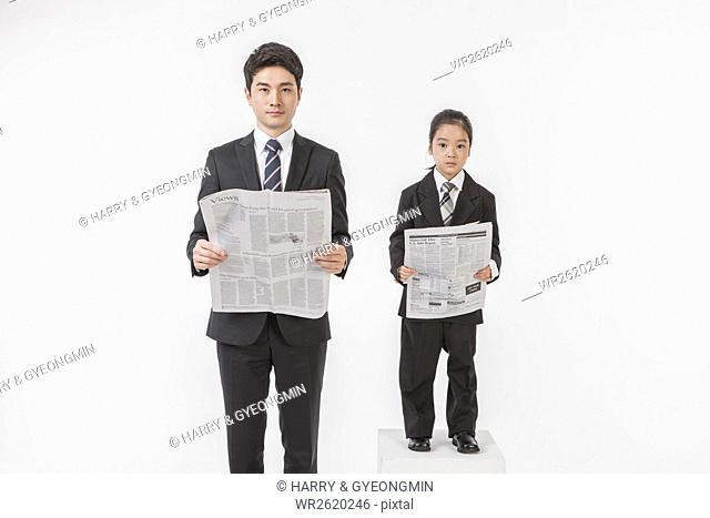 Businessman and his daughter with newspapers
