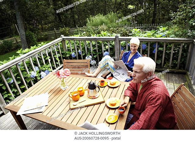 High angle view of a mature man and a senior woman sitting at the table