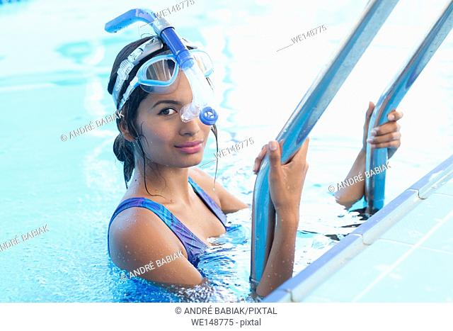 Young hispanic woman is entering the water for swim training with swimmer snorkel