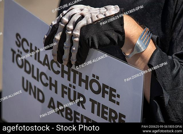 25 June 2020, Lower Saxony, Dissen: The activist of the animal protection organization Peta, dressed with a glove with skeleton imprint