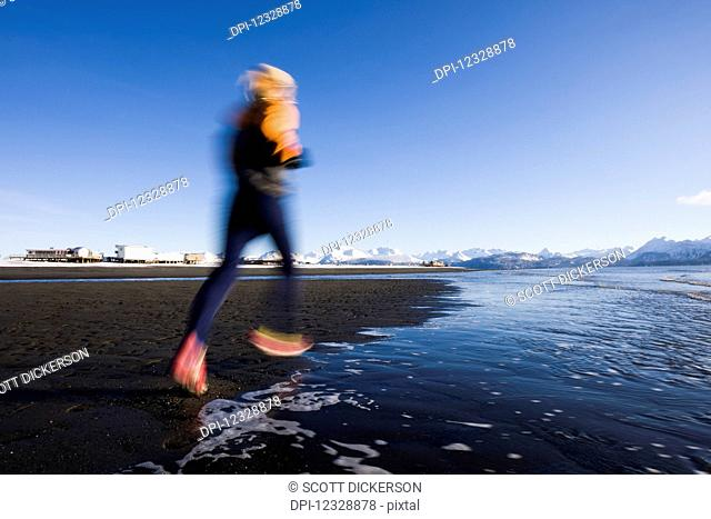A Young Woman Running Along The Water's Edge; Homer, Alaska, United States Of America