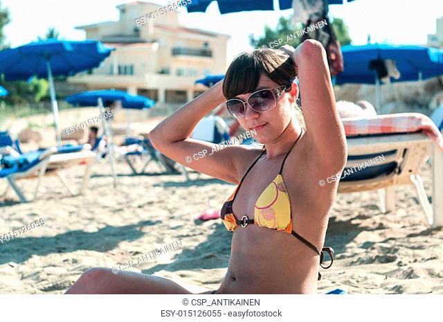 Joyous brunette woman in sunglasses tanning in sandy beach