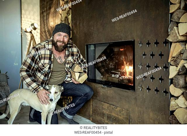 Portrait of smiling man with his dog in front of fireplace at home