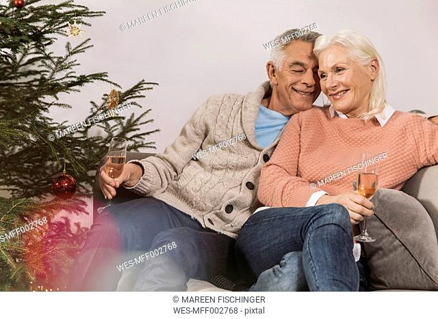 Senior couple sitting by Christmas tree drinking champagne