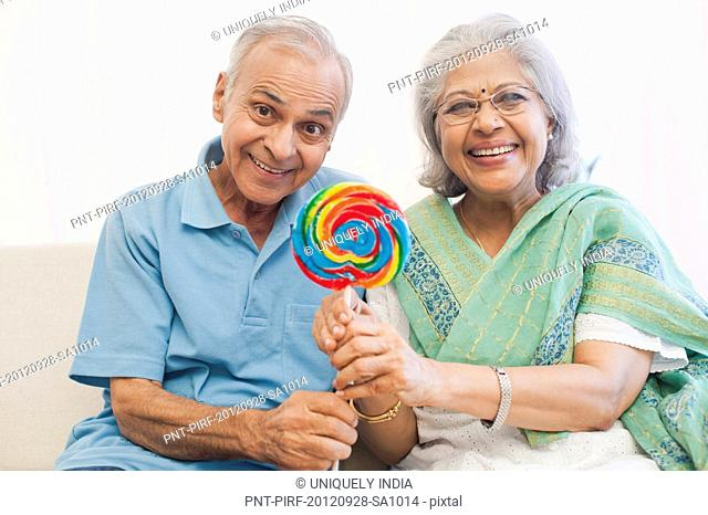 Senior couple holding a lollipop and smiling