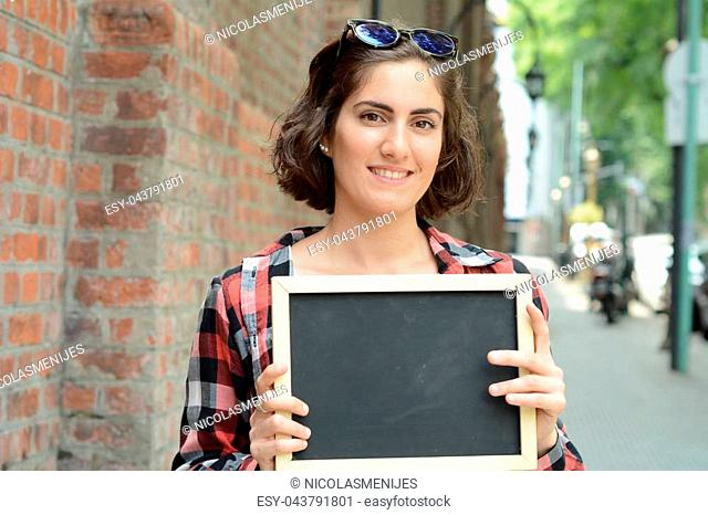 Portrait of a young beautiful woman holding chalkboard. Outdoors