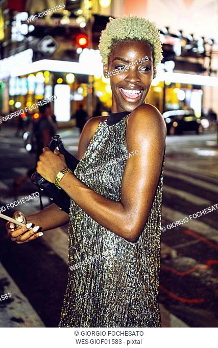 USA, New York City, portrait of happy young woman on Times Square at night